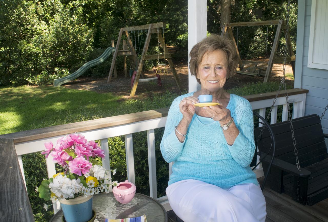 Betty Farr having tea on the playhouse porch